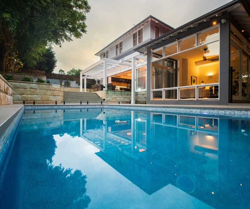 Backyard swimming pool with house in the background | Playoust Churcher North Shore Architects